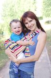 Mother carrys son in baby sling Royalty Free Stock Photography