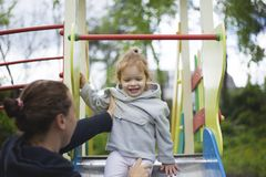 Mother catches daughter from a children slide, satisfied daughter contentedly on a children playground. Mother catches daughter from a children`s slide, happy stock photo