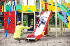 Mother catching son on playground slide Royalty Free Stock Photo