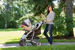 Mother With Cell Phone And Carriage Walking In Royalty Free Stock Image