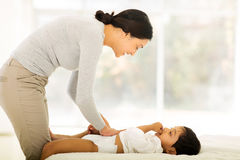 Mother changing baby nappy stock photography