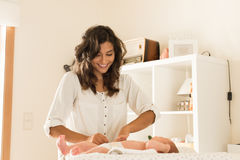 Mother changing baby`s diaper Royalty Free Stock Photography