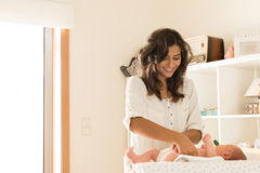 Mother changing baby`s diaper. Mother changing a diaper on newborn baby Stock Photos
