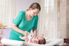 Mother Changing Diaper. Mother is changing diaper of her daughter Stock Photos