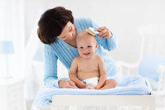 Mother changing diaper to baby boy Stock Photos