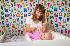 Mother changing diaper to her little baby in child room Royalty Free Stock Photography