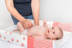 Mother is changing diaper to her little baby. In child room at home stock image