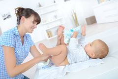 Mother changing diapers nine months old baby. Mother changing diapers of a nine months old baby Stock Photos