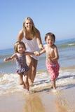 Mother Chasing Children Along Beach Stock Image