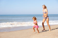 Mother chasing young girl on beach Royalty Free Stock Images