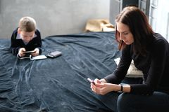 Mother chatting and her son playing games at the smart phone. Co stock image