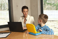 Mother checking boy's computer Stock Photography
