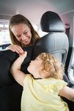 Mother checking her baby in the car seat Stock Photography