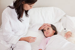 Mother checking on her daughter's temperature. In a bedroom Royalty Free Stock Photography
