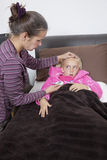 Mother checking unwell girl's temperature at home Royalty Free Stock Images