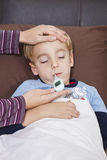 Mother checking unwell little boy's temperature with thermometer Stock Images