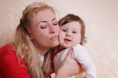 Mother cheek to cheek with one year baby girl Royalty Free Stock Photos