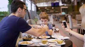 Mother is cheerfully taking picture of her child eating at the table while father is helping him stock footage