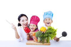 Chef family cook vegetable. Mother and chef children are ready to cook vegetable on white background royalty free stock photo