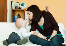 Mother and child. Young mother kissing her small child on a sofa Stock Image