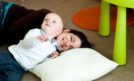 Mother and child. Young mother playing with her child on the floor Royalty Free Stock Photography