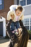 Mother and child. Caucasian mother holding up baby girl in front of house outside stock image