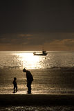 Mother and Child. Silhouette of a woman bending down towards a small child on a beach.  A fishing boat at sea can be seen in the background Stock Images