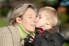 Mother and child. Portrait of little boy kissing his mother Royalty Free Stock Image