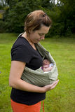 Mother And Child. A portrait of a mother holding her newborn baby outside in a sling Stock Photos