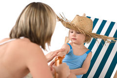 Mother with child apply suntan lotion on beach Royalty Free Stock Photography