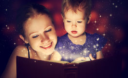Mother and child baby daughter reading magic book in dark Royalty Free Stock Photo