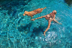 Mother with child on back swim with dog in pool Stock Photos
