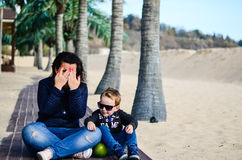 Mother and  child on the beach. Cute  fashion smiling boy sitting with his mom at wooden path on tropical beach Royalty Free Stock Photography