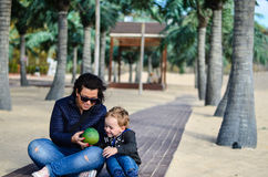 Mother and  child on the beach. Cute  smiling boy having fun with his mom at wooden path on tropical beach Stock Photography