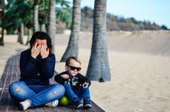 Mother and  child on the beach. Cute  smiling boy having fun with his mom at wooden path on tropical beach Royalty Free Stock Photo