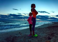 Mother and child on beach on sunset standing back to back Stock Image