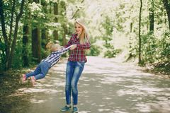 Mother with child. Beautiful long-haired mom walking in the woods with her little daughter royalty free stock photos
