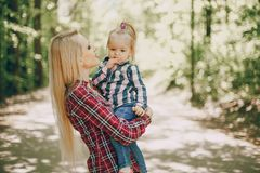 Mother with child. Beautiful long-haired mom walking in the woods with her little daughter royalty free stock photo