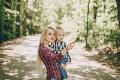 Mother with child. Beautiful long-haired mom walking in the woods with her little daughter stock photography