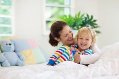 Mother and child in bed. Mom and baby at home stock photos