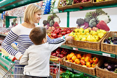 Mother and child with bell pepper in vegetables shop. Mother and child with bell pepper in vegetables department in the supermarket Stock Photo