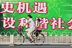 Mother and child on a bike passing a big billboard, Beijing, China Stock Photo