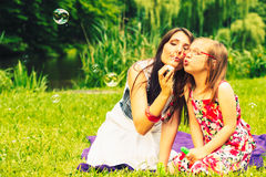 Mother and child blowing soap bubbles outdoor. Royalty Free Stock Images