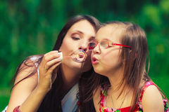 Mother and child blowing soap bubbles outdoor. Mother and daughter child blowing soap bubbles outdoor. Parent and kid having fun in park. Happy and carefree Stock Images