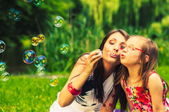 Mother and child blowing soap bubbles outdoor. Mother and daughter child blowing soap bubbles outdoor. Parent and kid having fun in park. Happy and carefree Royalty Free Stock Photo