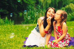 Mother and child blowing soap bubbles outdoor. Mother and daughter child blowing soap bubbles outdoor. Parent and kid having fun in park. Happy and carefree Stock Photos