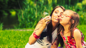 Mother and child blowing soap bubbles outdoor. Stock Photos