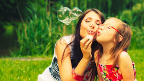 Mother and child blowing soap bubbles outdoor. Royalty Free Stock Photography