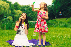 Mother and child blowing soap bubbles outdoor. Royalty Free Stock Image