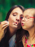 Mother and child blowing soap bubbles outdoor. Stock Images